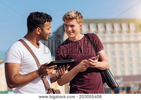 Let me search. Attractive brunette standing in semi position and holding tablet while looking at his friend