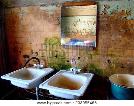 rusty destroyed bathroom sinks in poor house for the poor.