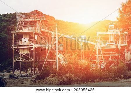 The ore processing plant or factory at the mining quarry in the sunset, industrial background