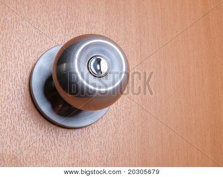 Color photo of a metal handle on a wooden door