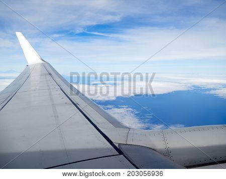 view of jet plane wing on the background of thick clouds and blue sky