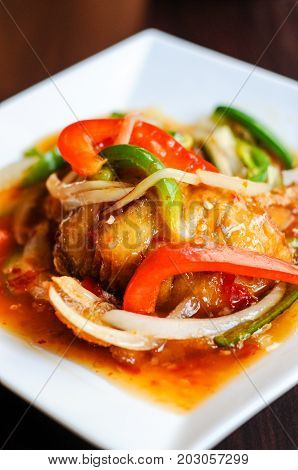 Red Hot Snapper, Fried red snapper fillet topped with hot peppers, onions, fresh garlic & bell peppers mixed in sweet & sour sauce.