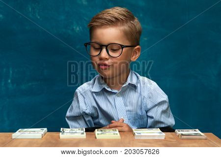 Cute fashionable child wearing eyeglasses sitting at the table and counting money. Little caucasin boy posing with cash imitating bookkeeper or businessman.