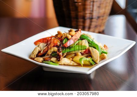 Stir-Fried Cashew Chicken, Slices of chicken breast stir-fried with cashew nuts, peapods, pineapple, onions, tomato ,and bell peppers
