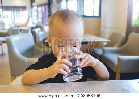 Portrait of Cute little Asian 18 months / 1 year old toddler baby boy child holding and drinking glass of water by himself