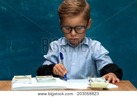 Concentrated little child wearing eyeglasses with cash in hands. Little boy posing on blue backdrop, imitating successful businessperson or bookkeeper at workplace.
