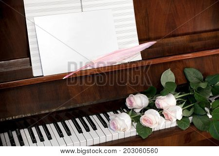 Composition from bouquet of pale pink roses, musical paper and white blank sheet with pink quill pen on brown piano.