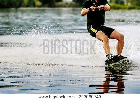 male wakeboarder rides on lake in wakeboard splashes of water