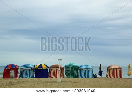beach in summer with tents sun and blue sky France Normandy city of Trouville
