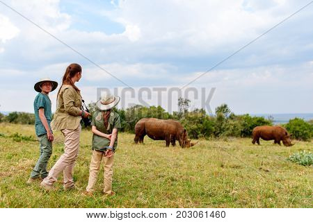 Back view of family on safari walking close to  white rhino