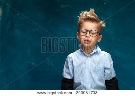 Portrait of funny little boy posing with closed eyes on blue backdrop. Little child imitating tired office worker or businessperson at workplace. Copyspace