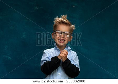 Happy smiling caucasian child wearing eyeglasses and shirt posing on blue backdrop. Funny little boy imitating office worker or businessman at workplace.