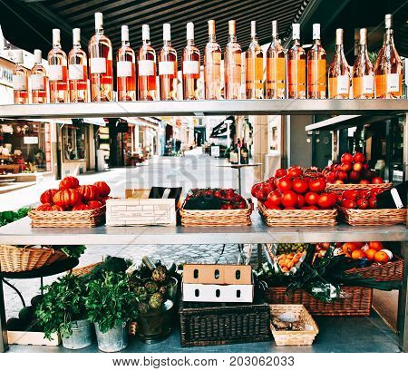 Market stand with vegetables, ripe fruits and wine on the street.