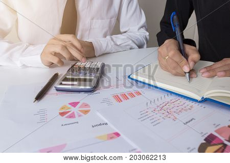 Two businessman colleagues discussing plan with financial graph data on office table with laptop Concept co working Business meeting