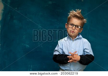 Funny little boy wearing eyeglasses and shirt imitating crazy office worker or businessperson. Portrait of cute boy posing on blue backdrop and looking at the camera. Copyspace