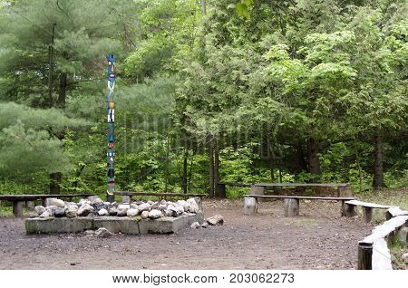 Large campfire pit with wooden benches and totem pole