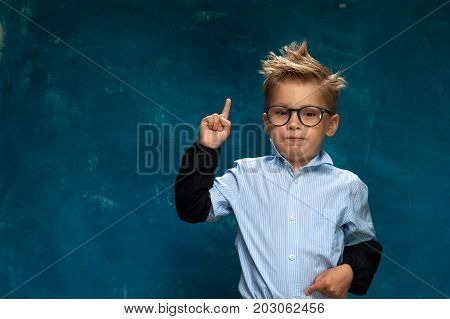Portrait of cute little child wearing eyeglasses and formal shirt imitating office worker or businessperson. Caucasian child posing on blue backdrop, pointing his finger to space. Copyspace