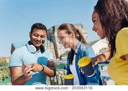 It is you. Handsome international young man pointing at his telephone while keeping smile on his face and standing near his fiends