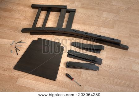 Assembling furniture at home parts of a wooden chair lie on the floor prepared for assembly.