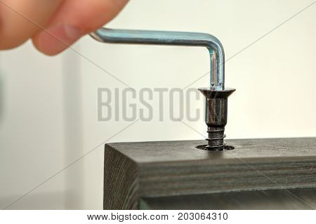 Screw the furniture screw into the wood plank using the hex key close-up.