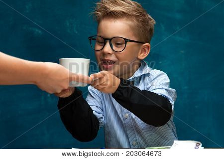 Portrait of stylish business child wearing eyeglasses sitting at workplace, having break with cup of drink. Cute caucasian boy imitating businessperson or office worker.
