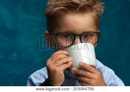 Closeup of cute child wearing eyeglasses posing with cup of drink. Stylish little boy imitating office worker or businessperson
