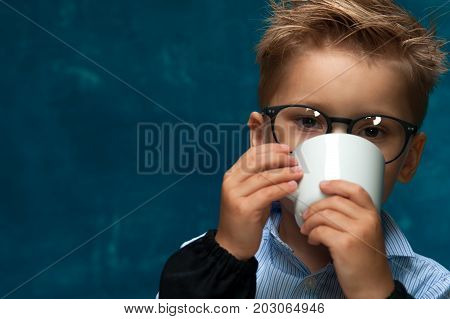 Closeup of cute child wearing eyeglasses posing with cup of drink. Stylish little boy imitating office worker or businessperson. Copyspace