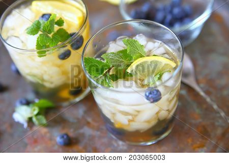 Glasses of green tea with crushed ice lemon blueberries and mint