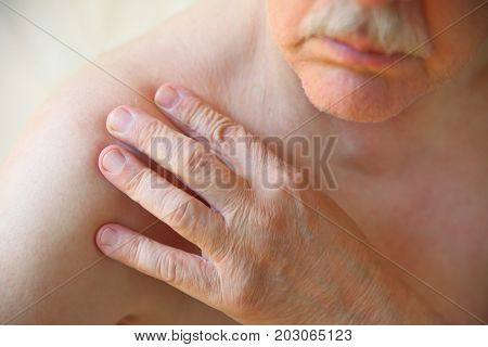 A senior man with his hand on a sore shoulder