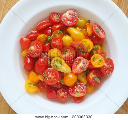 Assorted varieties and shapes of ripe cherry tomatoes marinating in a white dish from overhead