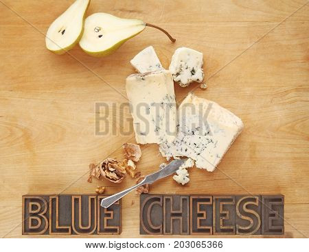 Blue cheese pieces with fresh pear walnuts and the words on a cutting board with copy space