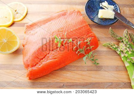 Fresh portion of salmon with lemon asparagus butter and fresh herbs on a cutting board