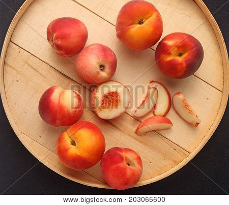 Fresh peaches whole and cut up on a round wooden lid