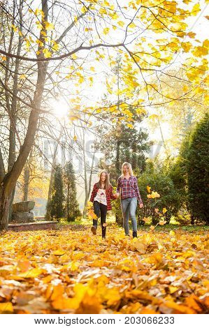 Walking with her best friend. Full length soft focus shot of a mother and daughter walking through the forest holding hands