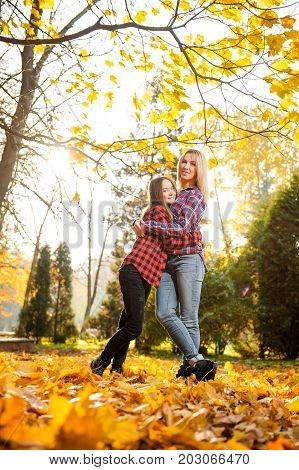 My role model. Low angle full length portrait of a beautiful happy mother hugging her teenage daughter posing in the sunlight in the forest