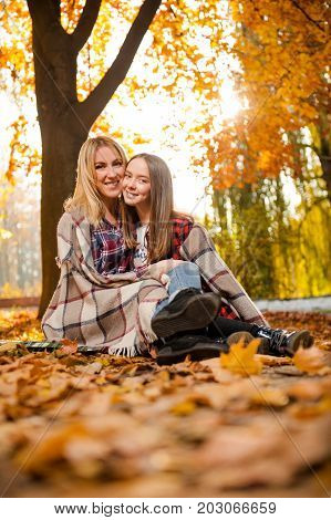 So alike. Gorgeous mother hugging her cheerful daughter both wrapped in a warm plaid relaxing outdoors together