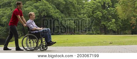 Common walk with disabled friend on wheelchair