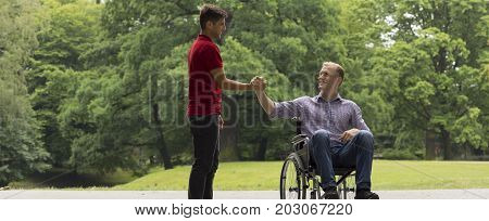 Disabled man greeting with friend in the park