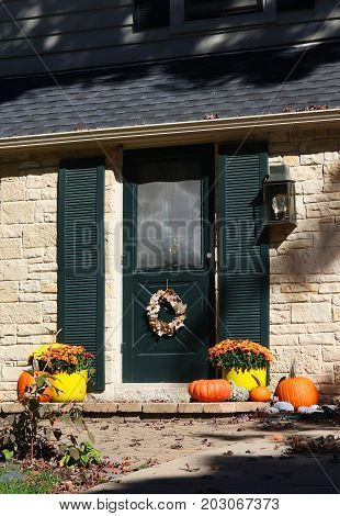 Sun lighted main entrance of the house decorated for autumn holidays season. Vertical composition.