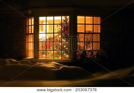 Welcome home Christmas tree in the window background. Night scene with a snow and brightly decorated Christmas tree in a window. Winter Holiday season background close up horizontal composition light blur.