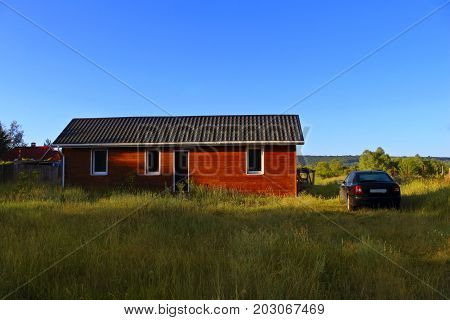 Wooden house in countryside. Ecological Small wooden house. Wooden house with meadow in front of it. Beautiful modern wooden house.