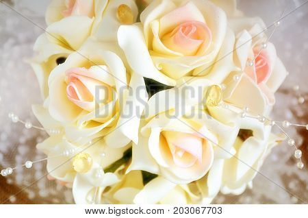 Decoration of a bridal bouquet from roses close up. Indoors. Horizontal format. Color. Photo.