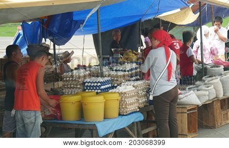 DAVAO ORIENTAL, PHILIPPINES--Sidewalk vendors sell their produce from their makeshift tents at the street market in Banaybanay, Davao Oriental in March 2016. Popular are eggs, anchovy and dried fish.