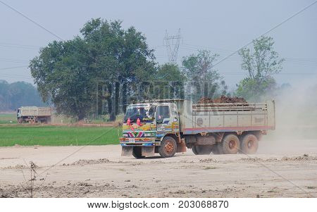 THAILAND--A dump truck loaded with earth kicks off dust at a road being repaired in the northern part of Thailand in March 2016.