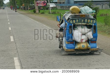 DAVAO  DEL NORTE, PHILIPPINES--A blue tricycle, or motorcycle with sidecar overloaded with various cargo at the national highway in Mabini, Davao del Norte, southern Philippines in March 2016.