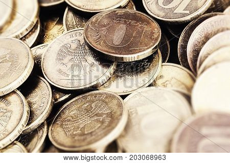 Ten-ruble coins of bank of Russia close up in a zone of sharpness and blur. Horizontal format. Indoors. Photo color.