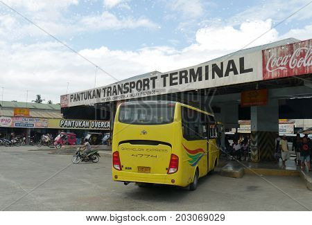 COMVAL PROVINCE, PHILIPPINES--A yellow Bachelor Express bus takes a short stop at the Pantucan Transport Terminal in Compostela Valley Province, Philippines in March 2016.