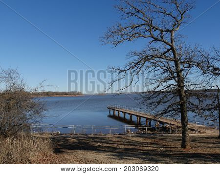 Leafless tree with a wooden dock with railings over Thunderbird Lake State park on a cold day