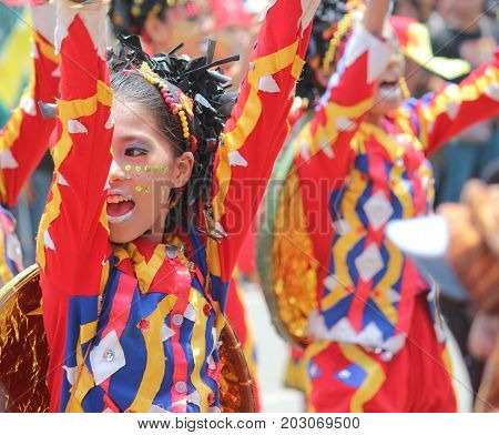 DAVAO CITY, PHILIPPINES--AUGUST 2014: A girl with sequins in her face dancing in the streets. Kadayawan is celebrated August each year to give thanks for life and an abundant harvest.