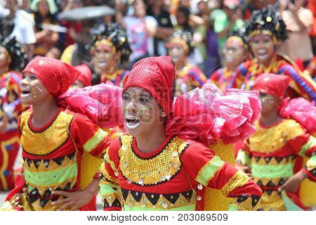 DAVAO CITY, PHILIPPINES--AUGUST 2014: Streetdancers in colorful costumes dance in the streets at the parade. Kadayawan is celebrated August each year to give thanks for life and an abundant harvest.